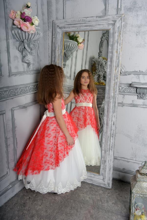 Type est la fille la brune dans le blanc avec une robe ?l?gante rouge image libre de droits