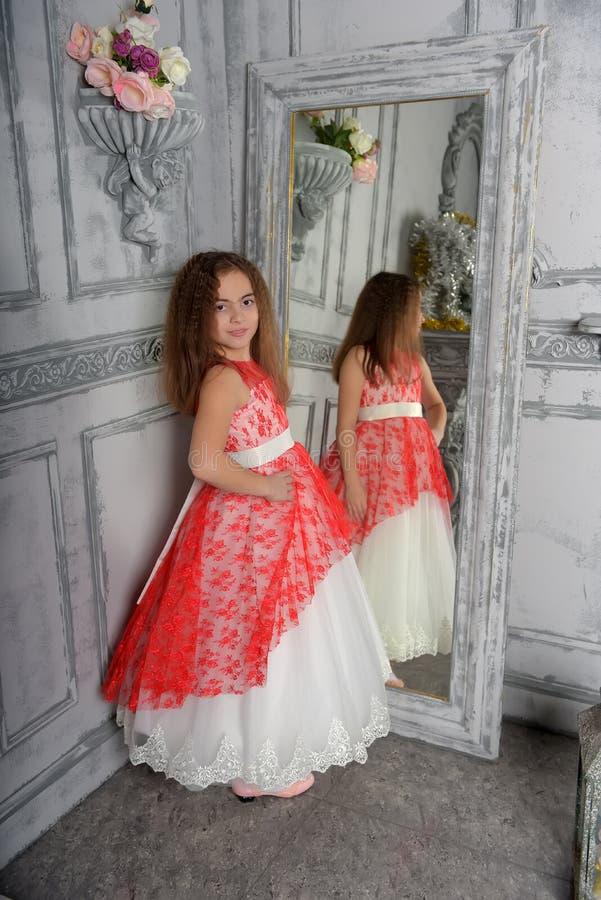 Type est la fille la brune dans le blanc avec une robe ?l?gante rouge photo libre de droits