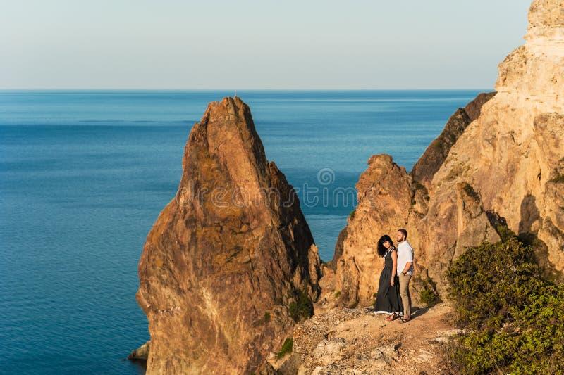 Type et fille à la mer étreignant au bord de la falaise image stock