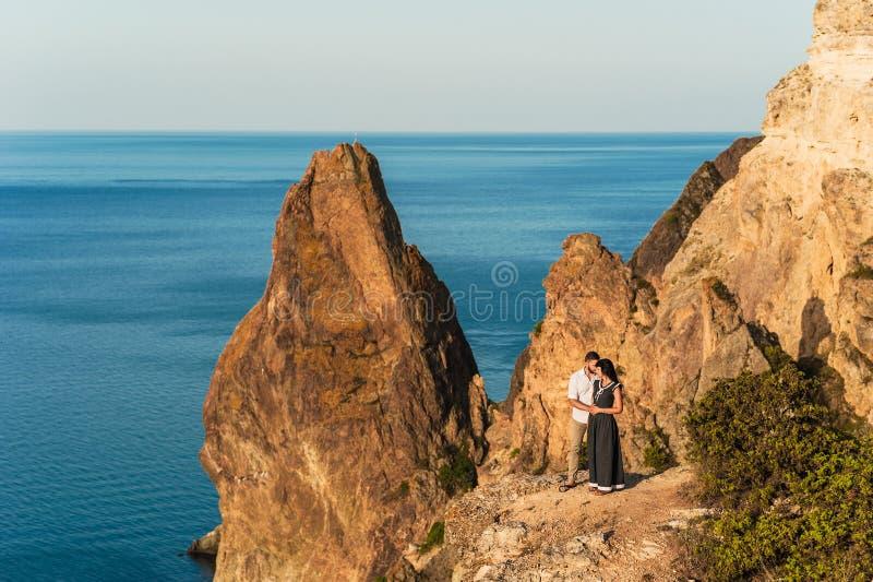 Type et fille à la mer étreignant au bord de la falaise image libre de droits