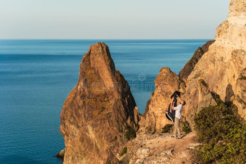Type et fille à la mer étreignant au bord de la falaise photographie stock