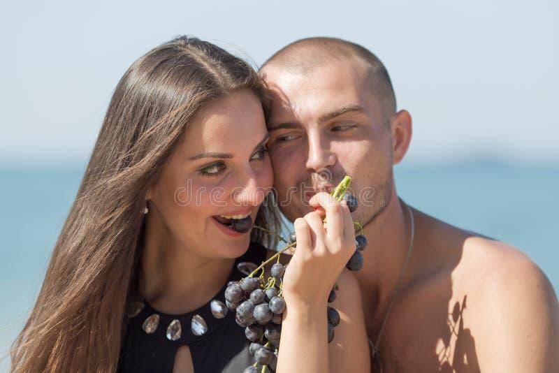 Type et fille mangeant les raisins noirs regardant chacun autre photographie stock