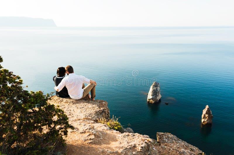 Type et fille s'asseyant au bord d'une falaise par la mer image libre de droits