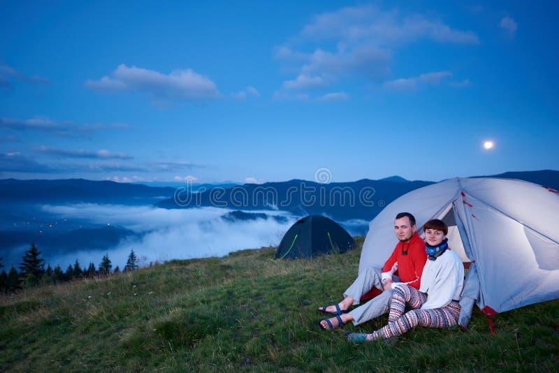 Type et fille s'asseyant dans la tente à l'aube avec la vue du beau paysage photographie stock libre de droits