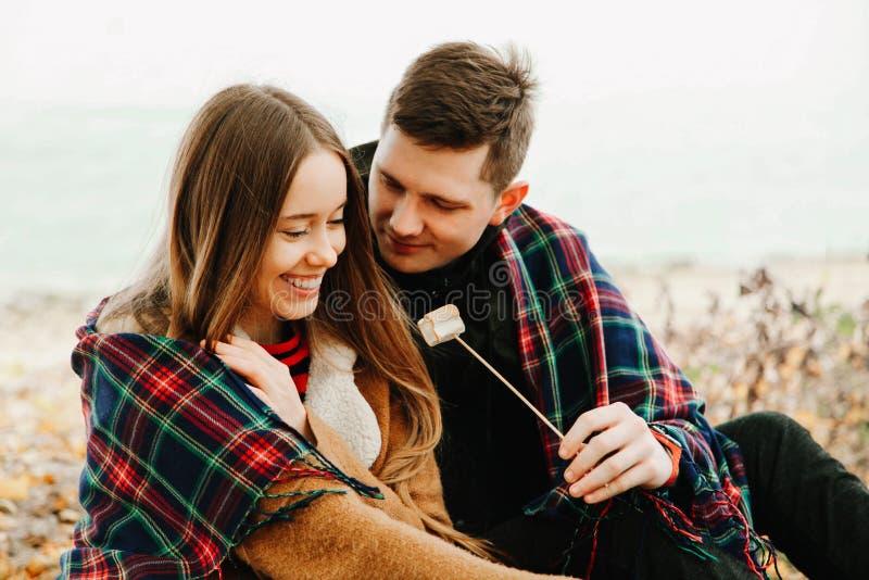 Type et une fille mangeant des guimauves photo stock