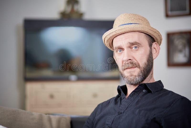 Type frais avec la barbe et chapeau regardant à l'appareil-photo à la maison photo stock