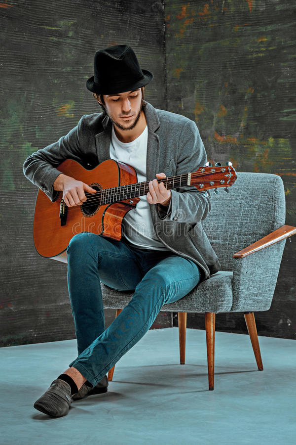Type frais avec le chapeau jouant la guitare sur le fond gris image stock