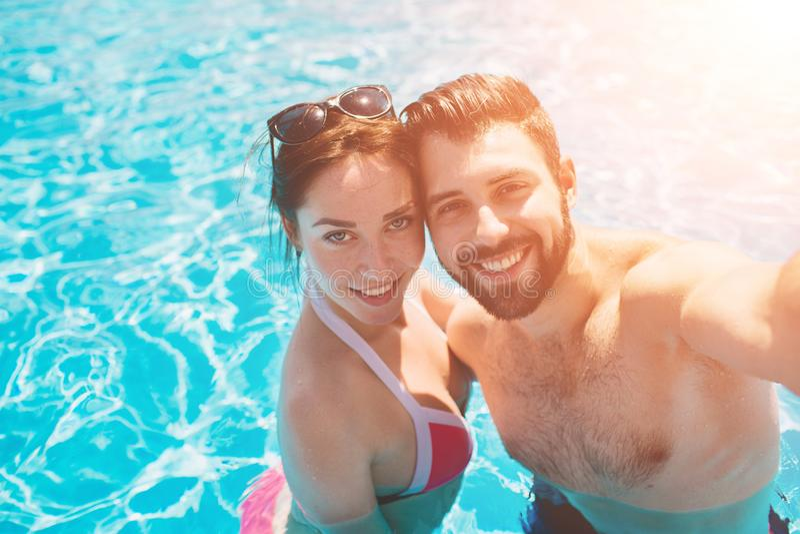 Type gai et dame jeunes se reposant tandis que piscine extérieure Couples dans l'eau Les types font le sephi d'été photos stock