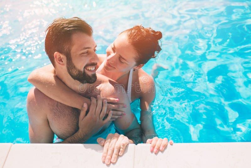 Type gai et dame jeunes se reposant tandis que piscine extérieure Couples dans l'eau Les types font le sephi d'été images stock