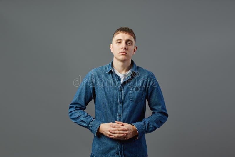 Type habillé dans un T-shirt blanc, les jeans et la chemise de jeans se tenant avec ses bras pliés dans le studio sur le fond gri photos stock