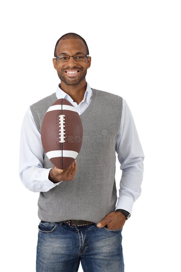 Type heureux avec le football américain photo stock