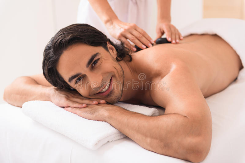 Type heureux bénéficiant du traitement par la masseuse photos stock