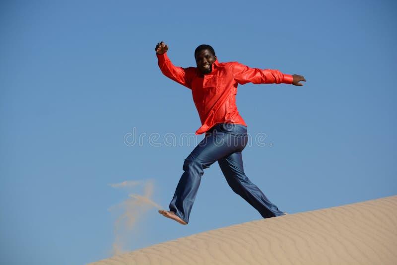Type heureux courant en bas de la dune photographie stock