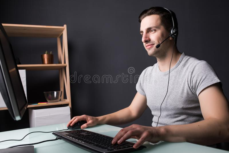 Type heureux devant le moniteur avec le casque à la maison images libres de droits
