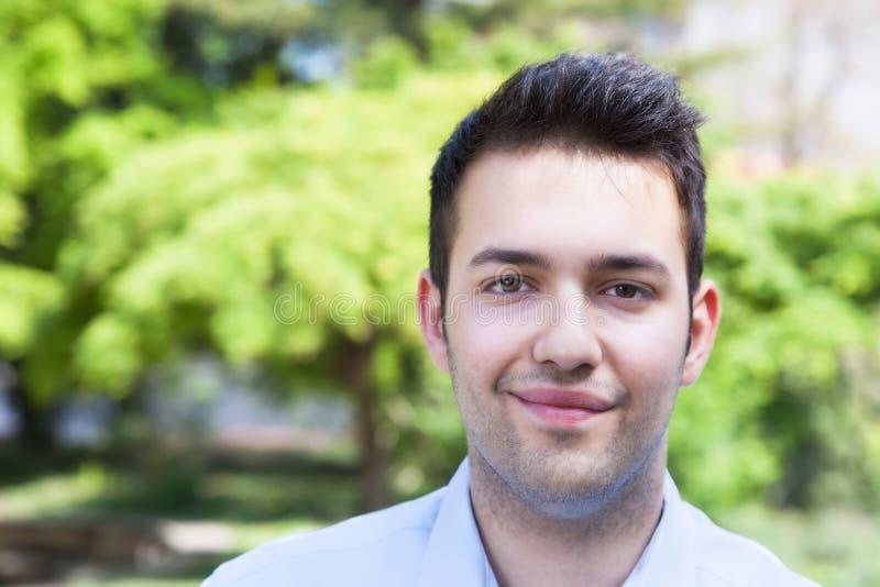 Type hispanique de sourire dans une chemise bleue dehors en parc photographie stock libre de droits