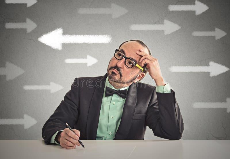 Type incertain regardant des flèches Homme complètement de l'hésitation de doutes images stock