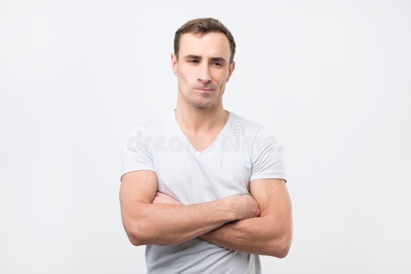 Type italien triste dans le T-shirt blanc regardant pensivement de côté photo libre de droits