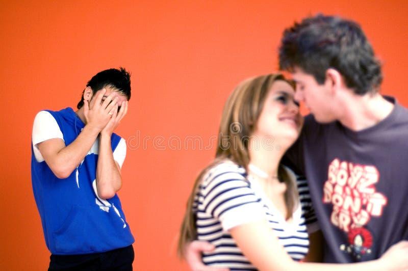 Type jaloux, embrassement de couples images stock