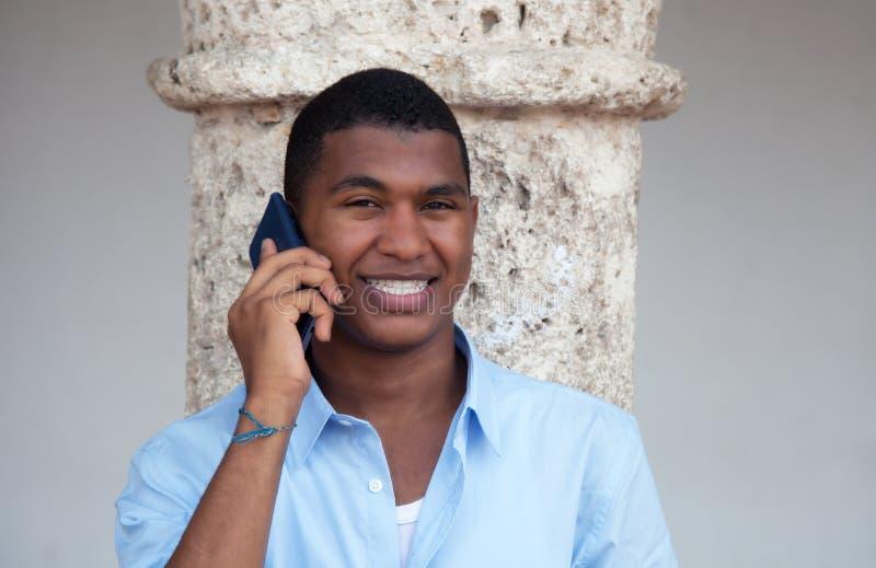 Type latin attirant avec le téléphone dans une ville coloniale photos stock