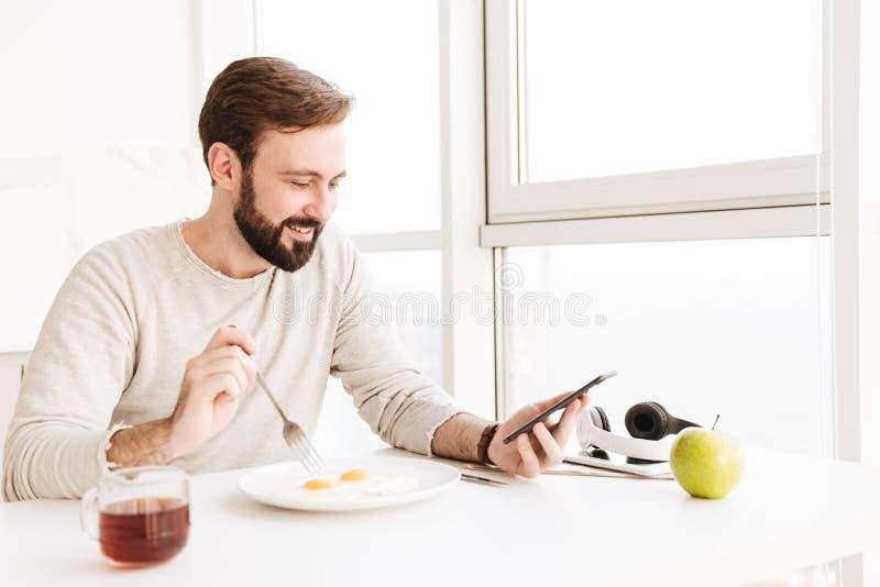 Type mûr heureux mangeant faisant frire des oeufs et à l'aide du téléphone portable, tandis que image libre de droits