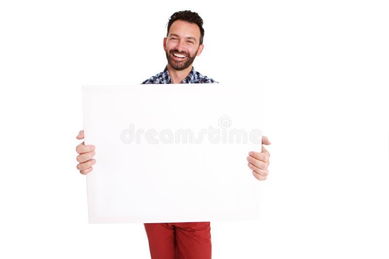 Type mûr heureux montrant le signe vide d'affiche photographie stock