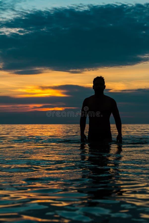 Type marchant de la plage sous le coucher du soleil photo stock