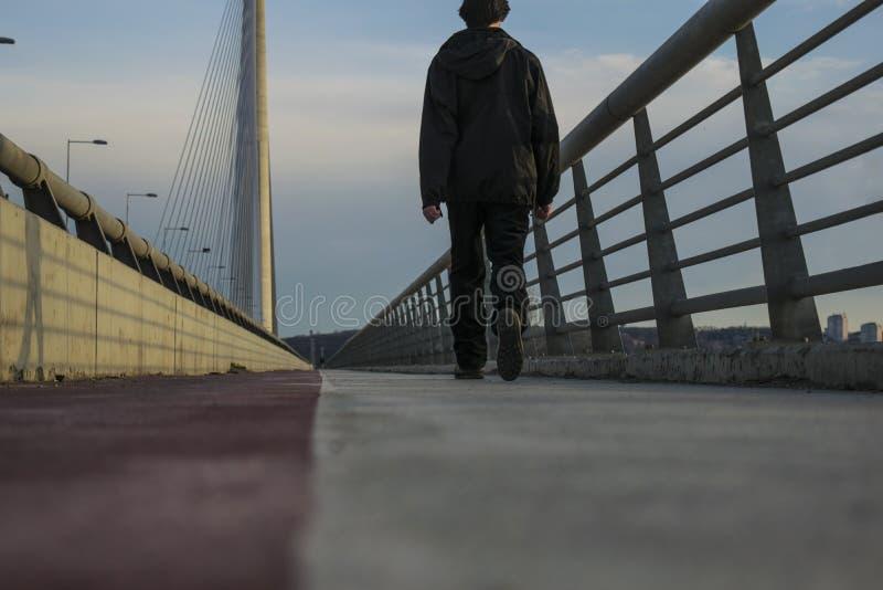 Type marchant sur le pont d'ADA à Belgrade photo libre de droits