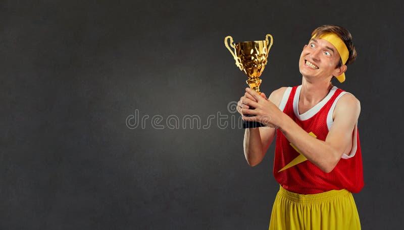 Type mince et drôle avec une tasse du ` s de champion dans des ses mains photo stock
