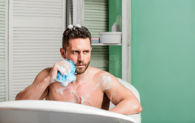 Type musculaire beau d'homme d?tendant dans le bain Concept de bien-?tre de station thermale Prise du bain avec des lessives de s images libres de droits