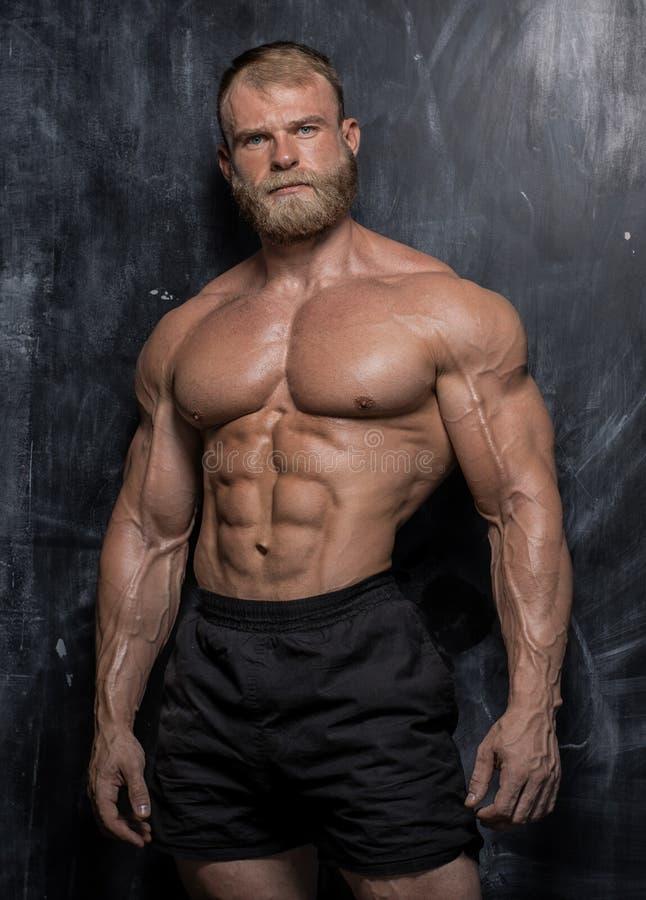 Type musculaire de bodybuilder au-dessus de fond foncé image stock