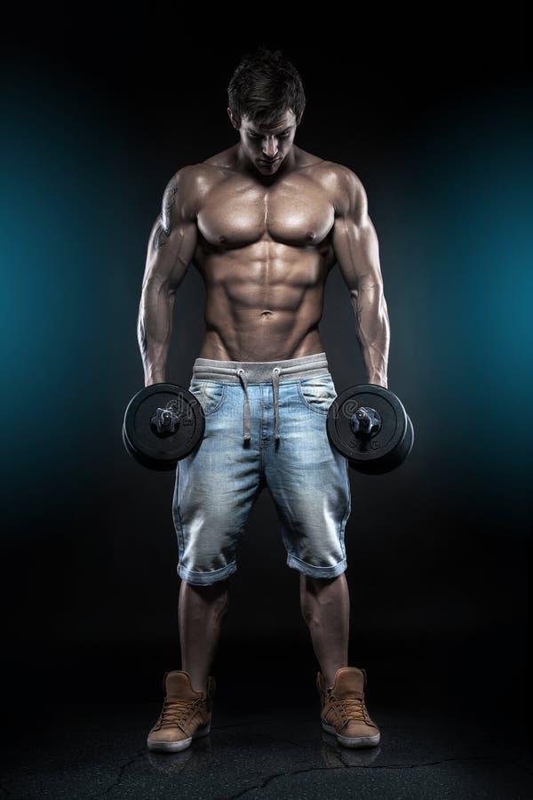 Type musculaire de bodybuilder faisant des exercices avec des haltères au-dessus de bla photos libres de droits