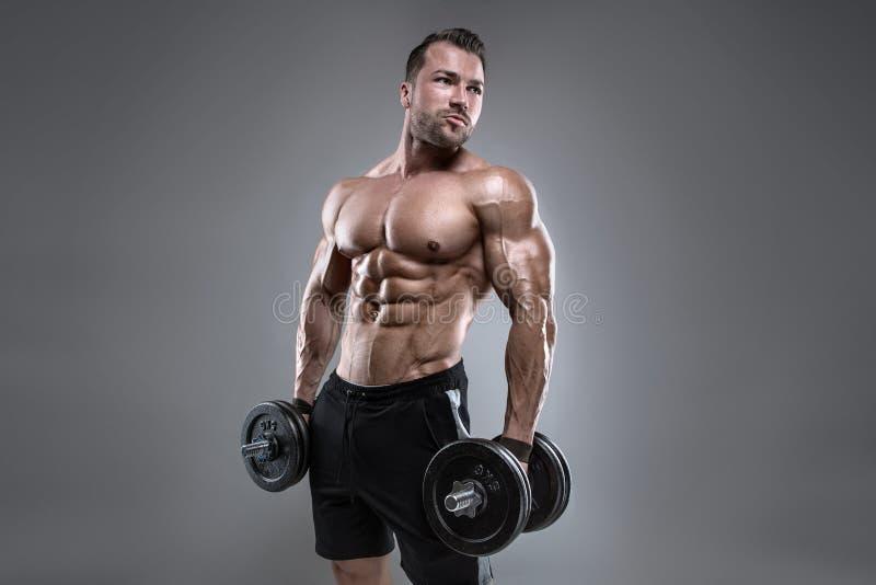 Type musculaire de bodybuilder faisant des exercices avec l'haltère photo stock