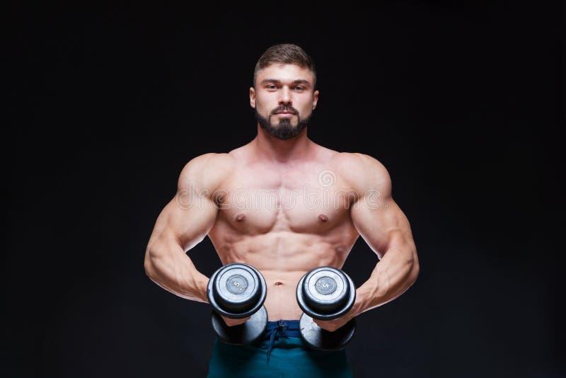 Type musculaire de bodybuilder faisant des exercices avec l'haltère au-dessus du fond noir photo libre de droits