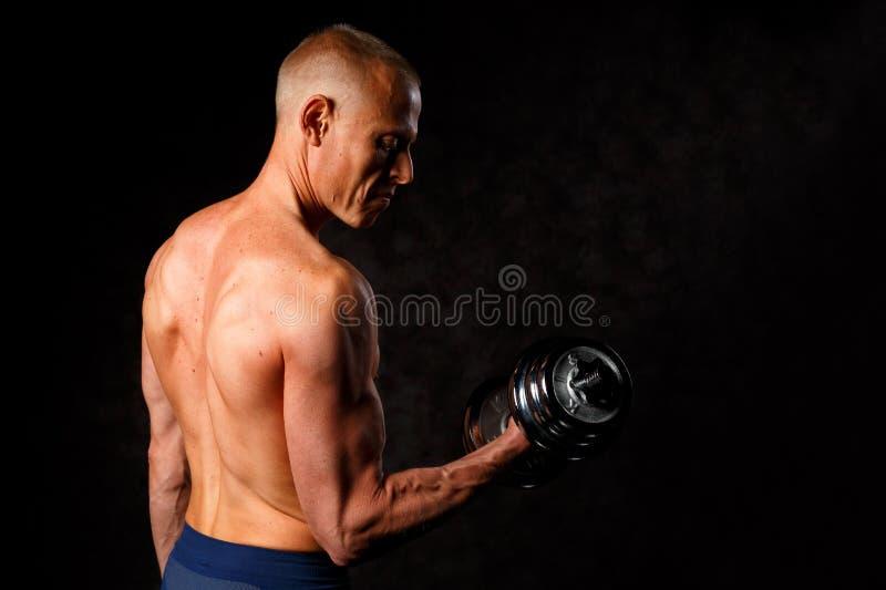 Type musculaire de bodybuilder faisant des exercices avec l'haltère au-dessus du fond noir photographie stock libre de droits