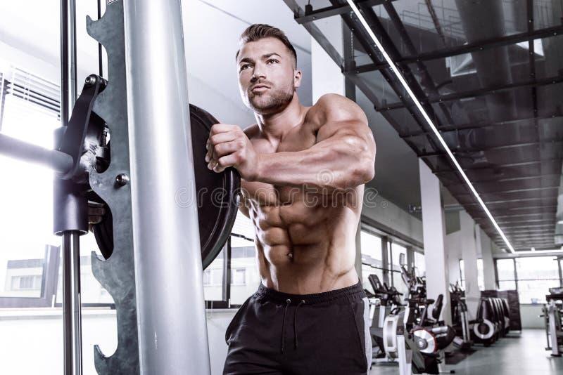 Type musculaire de bodybuilder faisant des exercices avec l'haltère sur le multip photo libre de droits