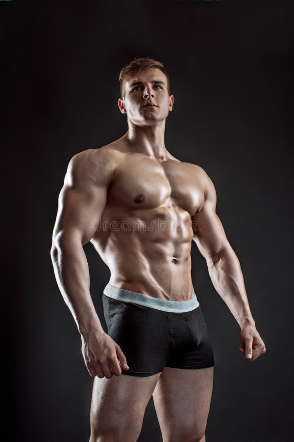 Type musculaire de bodybuilder faisant la pose au-dessus du fond noir image stock