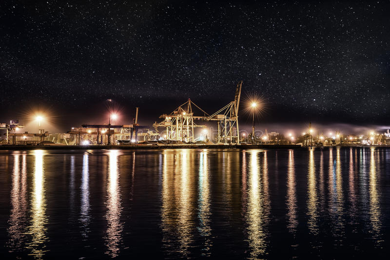 Type of night port. Working freight cranes, a ship at the pier, work in the port.Night photo, starry sky. Beautiful reflection of lights in the sea water stock image