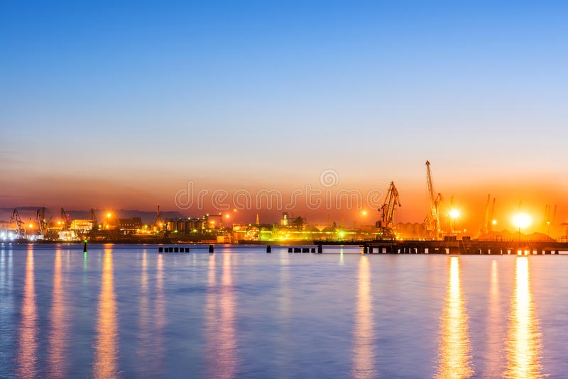 Type of night port. Working freight cranes, a ship at the pier, work in the port. Night photo view of the loading. Beautiful reflection of lights in the sea royalty free stock photo