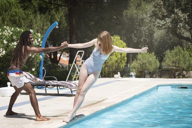 Type noir avec des dreadlocks jouant dans une piscine avec la fille caucasienne photo stock