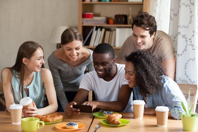 Type noir heureux montrant les vidéos drôles sur le smartphone images libres de droits