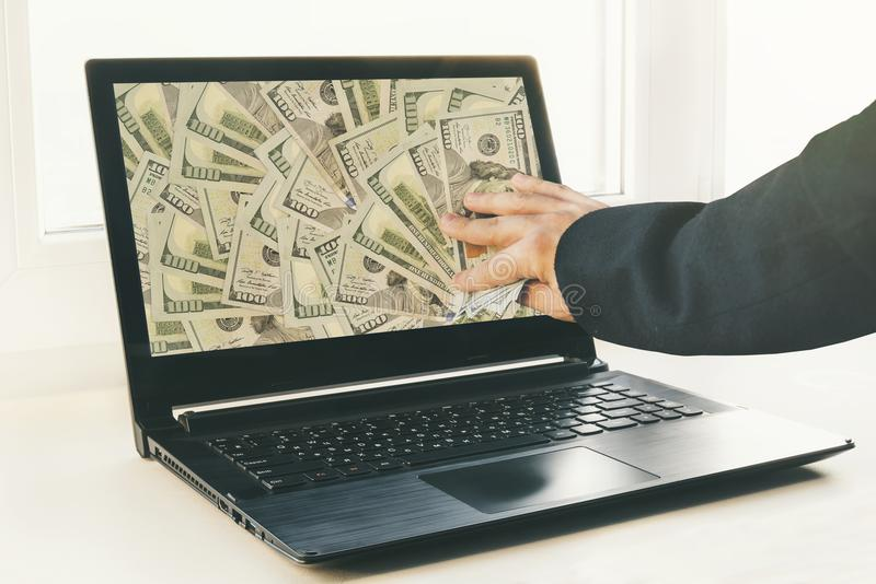 Type ou homme d'affaires tenant l'argent de mâle dans sa main Ordinateur portable à l'arrière-plan photos libres de droits