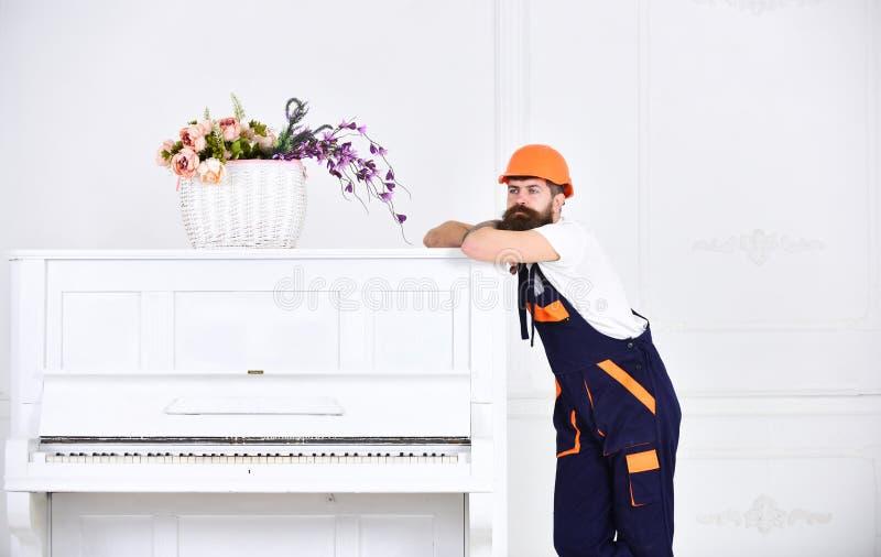 Type réfléchi se penchant sur le dessus du piano blanc de vintage avec le vase à fleur en verre d'isolement sur le fond blanc bar photos stock