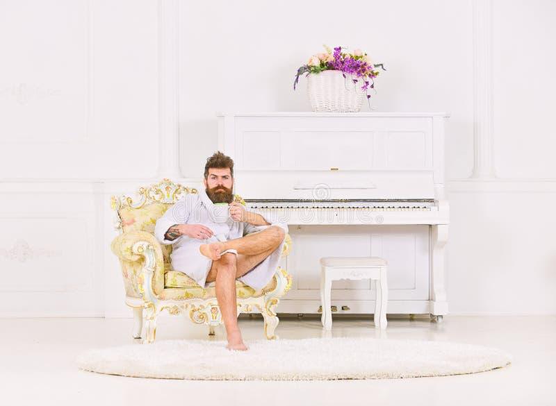 Type riche s'asseyant dans le fauteuil et le thé ou le café potable Type barbu dans la chambre blanche Concept parfait de matin photos libres de droits