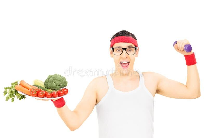Type ringard tenant le plat avec des légumes et une haltère image stock