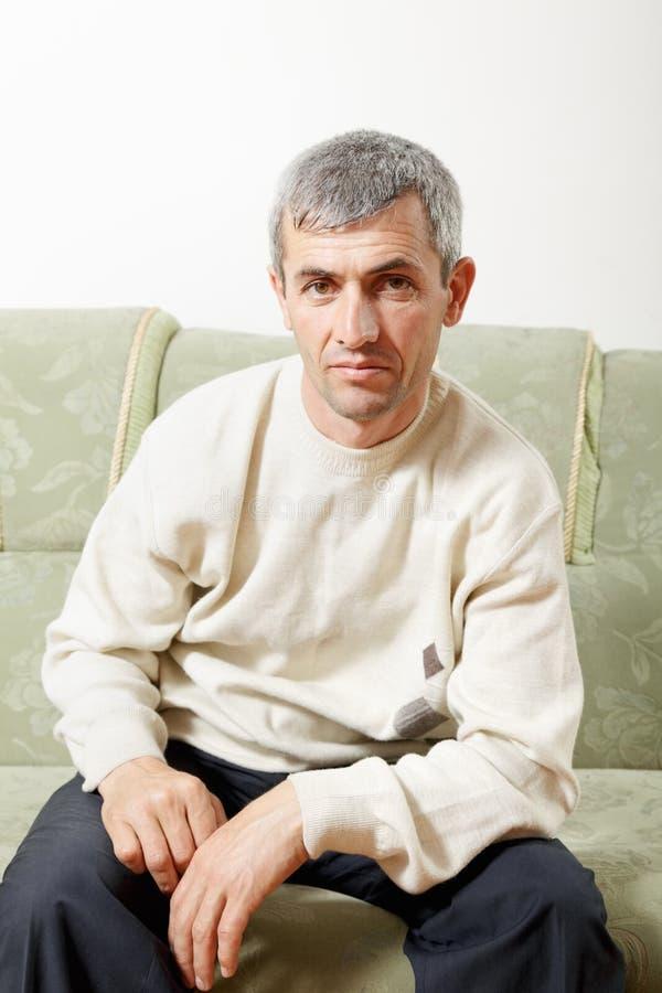 Type s'asseyant sur le sofa photographie stock libre de droits