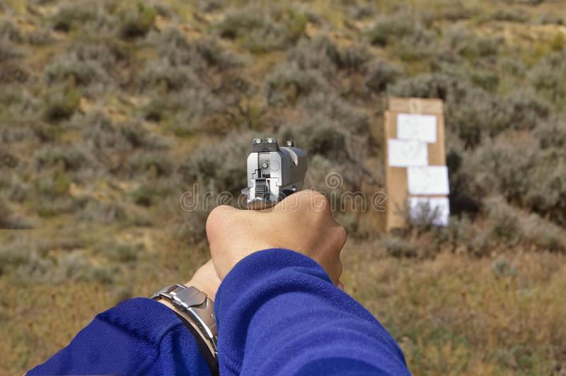 1911-type semi-automatic pistol in a two-hand hold aimed at a cardboard target on an outdoor range stock photography