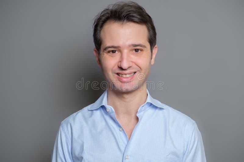 Type souriant en portrait bleu de chemise sur le fond gris image stock