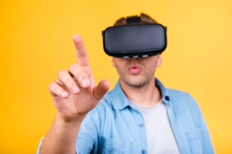 Type stupéfait dans les lunettes de port de réalité virtuelle de chemise de jeans, employant photo libre de droits