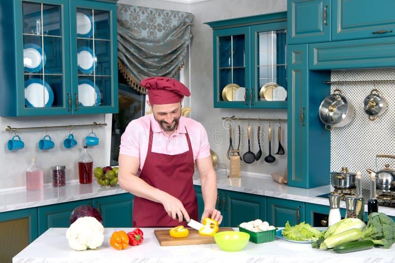 Type très souri et barbu dans le tablier et chapeau coupant le paprika jaune pour la salade photographie stock
