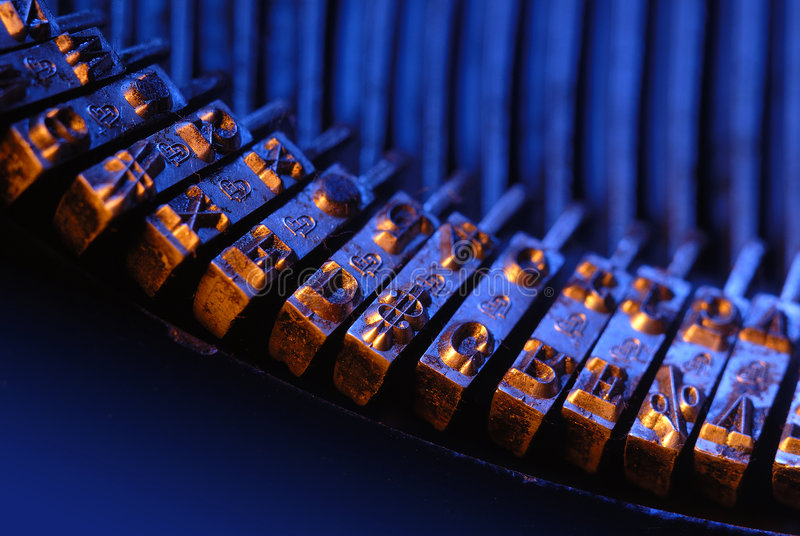 Typebar in blue and orange. The typebar from a vintage typewriter shot closeup with limited depth of field and lit with blue and orange lights stock images